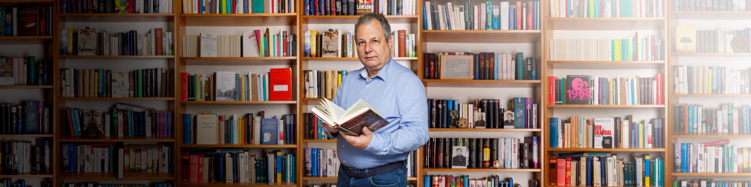 Rainer Schöttle vor Bücherwand